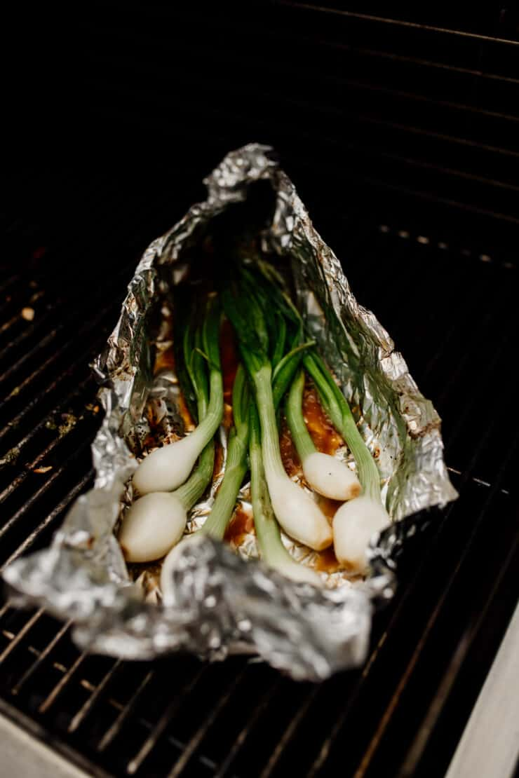 foil packet of green spring onions on the grill for making cebollitas asadas