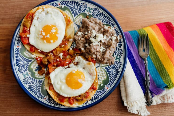 finished huevos rancheros on an earthenware plate with a silver fork on a rainbow striped placemat
