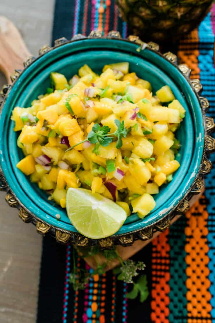 turquoise serving bowl filled with pineapple mango salsa with a quartered lime as garnish