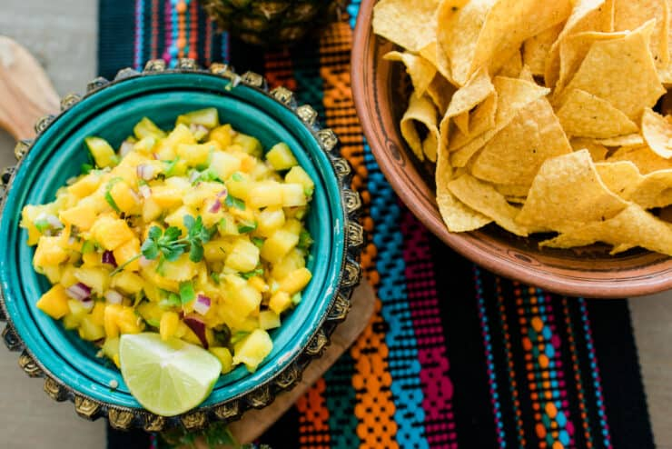 bowl of pineapple mango salsa next to a bowl of tortilla chips on a wooden table