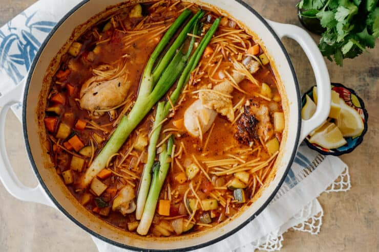 large pot of Fideo con pollo on a white and blue runner