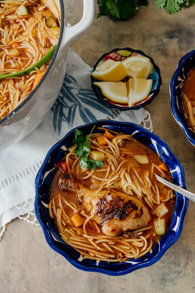Sopa de Fideos con Pollo, a Mexican version of chicken noodle soup in a Mexican blue bowl with a side of lemons