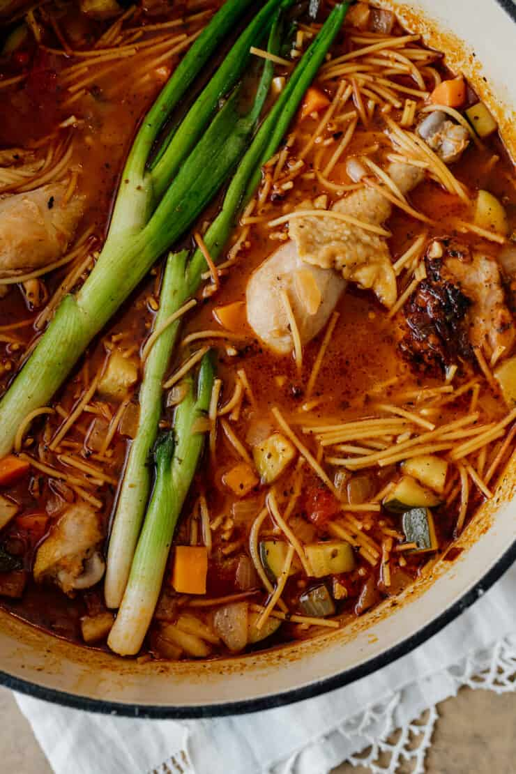 tight shot of fideos con pollo in a pot with green onions on top