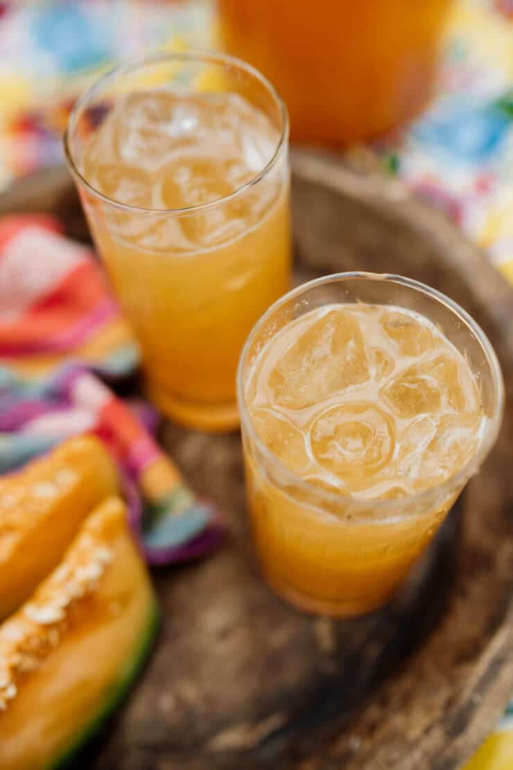 two glasses of iced Agua de Melón (Melon Water) on a wooden tray with slices of fresh cantaloupe