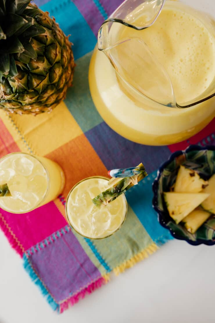 overhead shot of a pitcher filled with pineapple agua fresca next to two glasses of agua de pina and a fresh pineapple