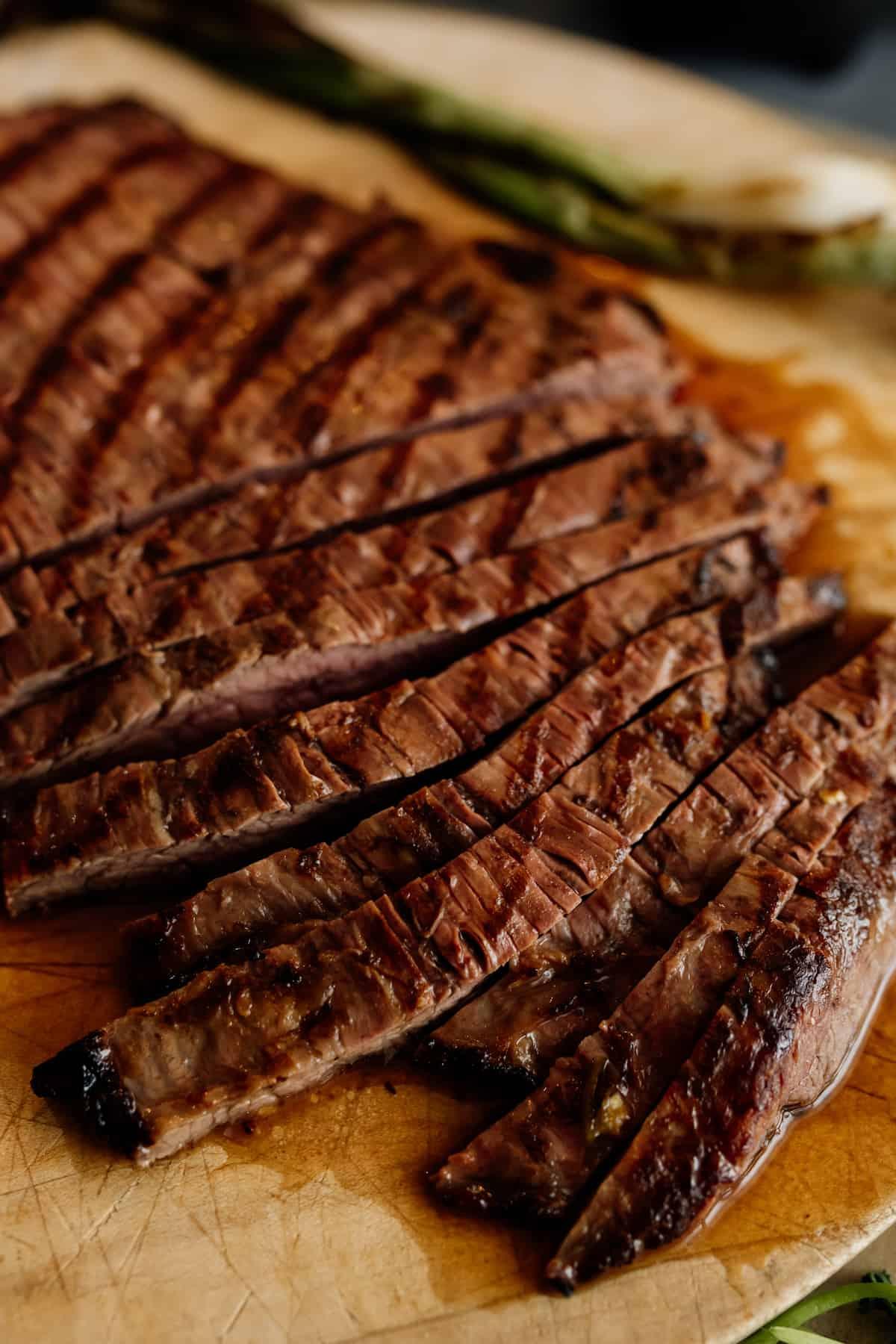 carne asada flank steak on a cutting board being sliced