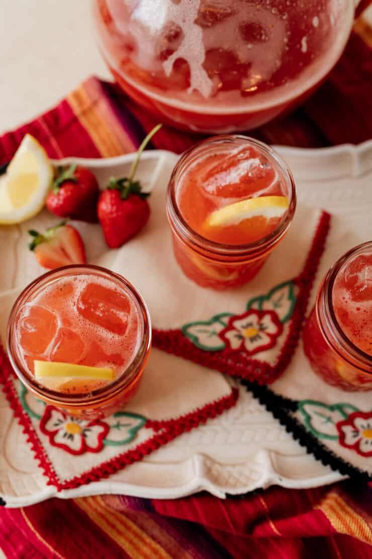 close up shot of strawberry sweet tea in a mason jar garnished with a fresh lemon slice
