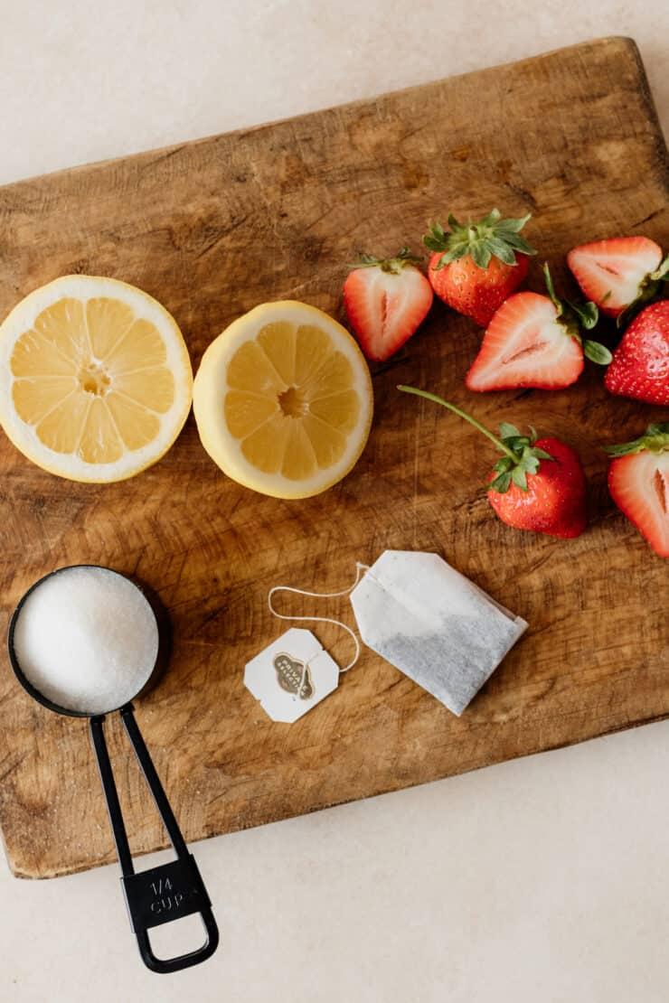 tea bag, sugar, halved lemon and strawberries on a wooden board
