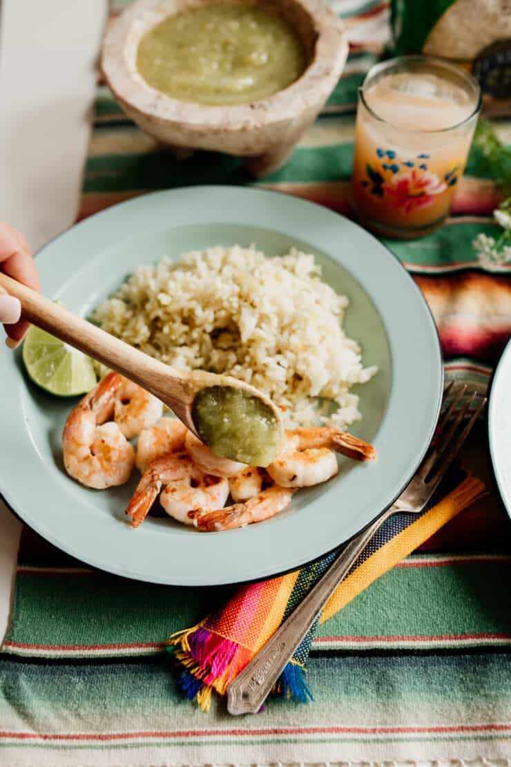 drizzling salsa verde on shrimp on a table setting with serape