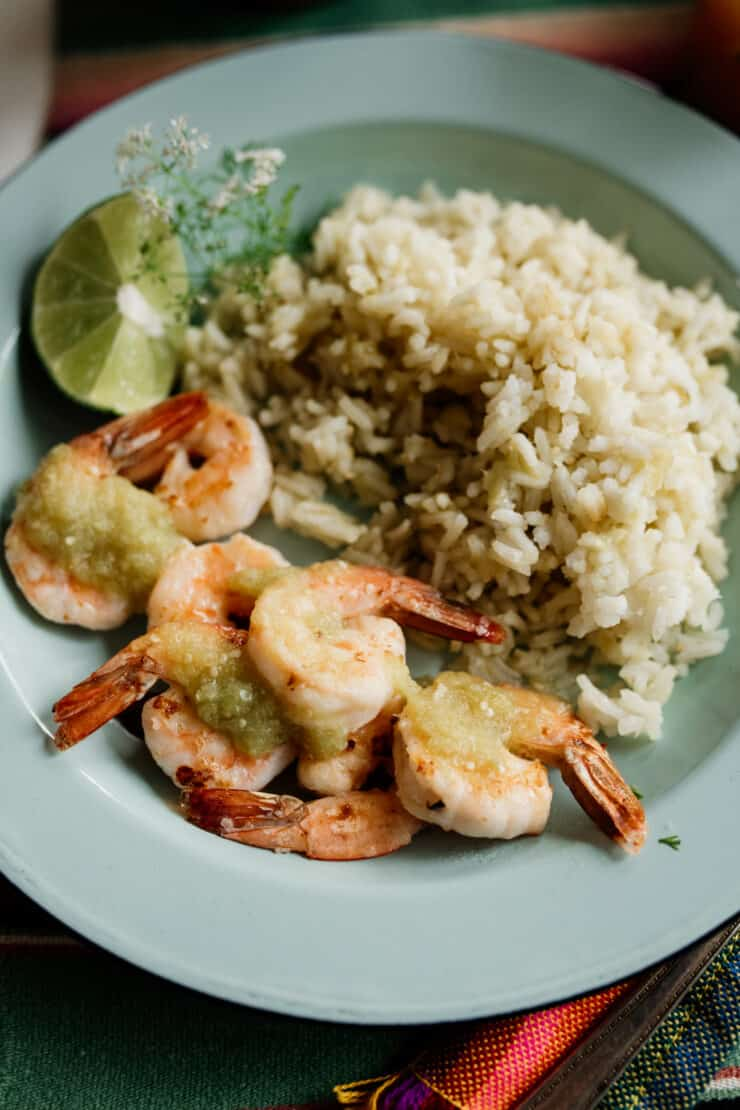 shrimp served with Mexican green rice and drizzled with bright and flavorful salsa verde on a teal enamel plate with a lime wedge