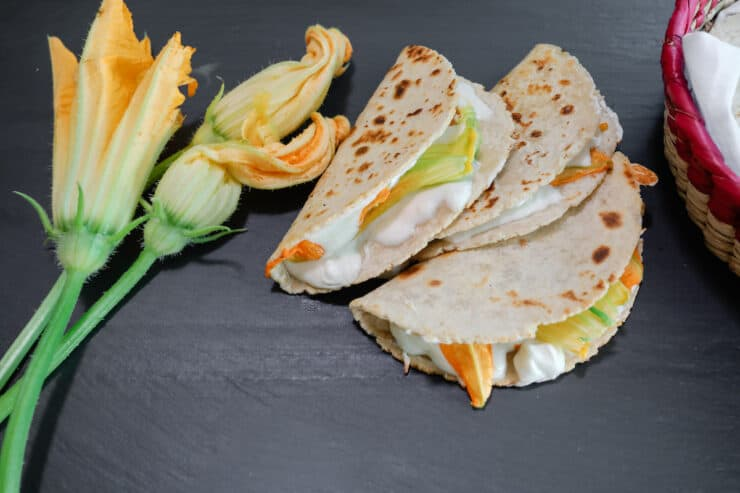squash blossom quesadillas on a black slate board with squash blossoms on the side