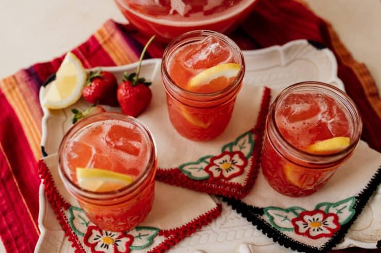 three mason jars of strawberry sweet tea on hand embroidered cocktail napkins