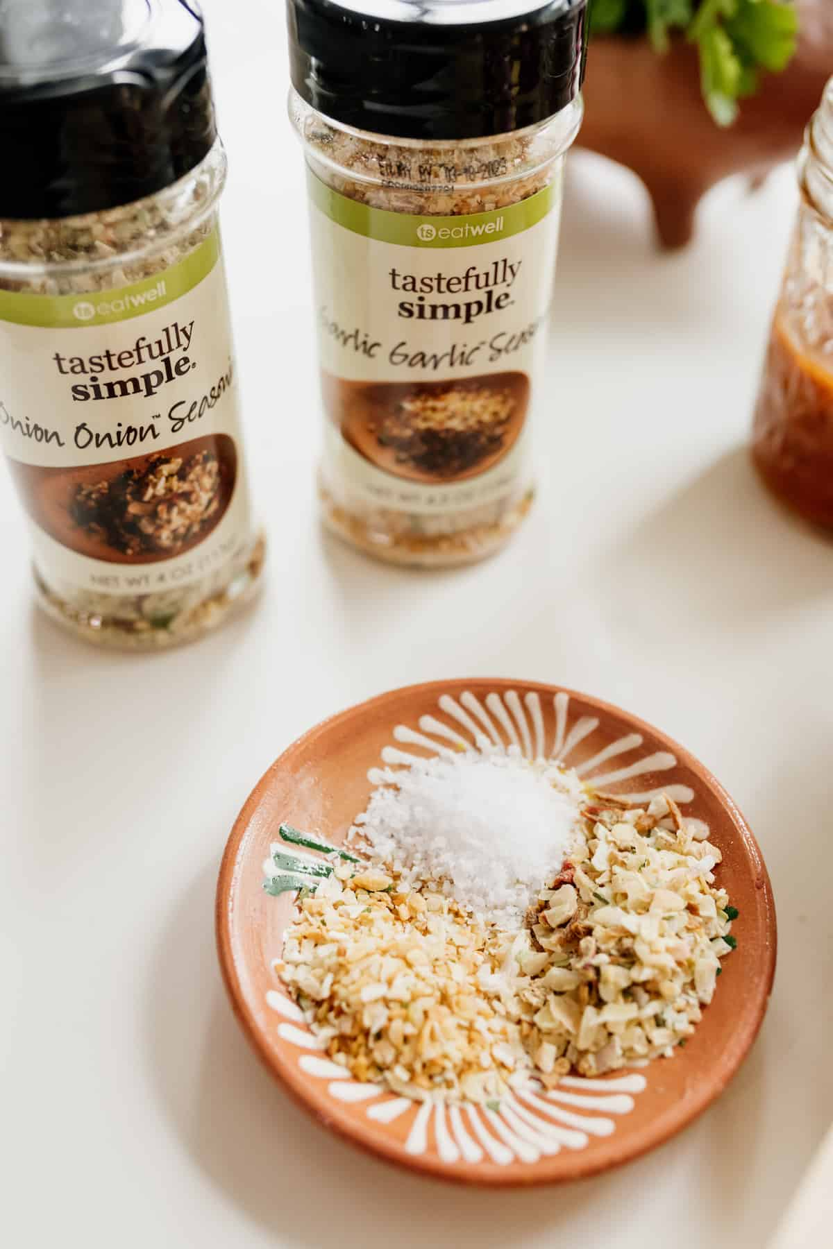 tastefully simple seasoning blends in their bottles and a small dish of spices