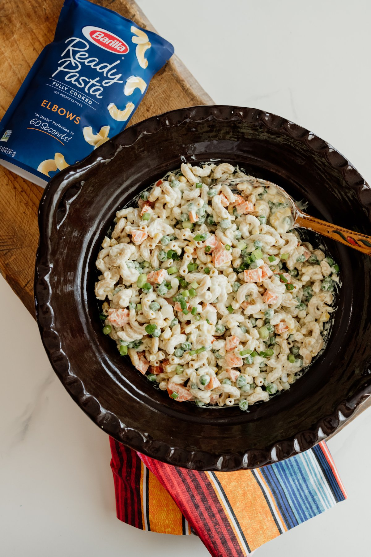 Ensalada de Coditos (Macaroni Salad) in a Mexican brown barro bowl with wooden spoon and striped napkin and a pouch of Ready Pasta by Barilla