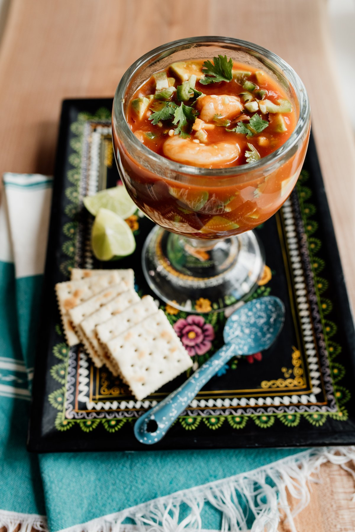 mexican shrimp coctel de camarones in a glass on a rectangular black plate with saltines