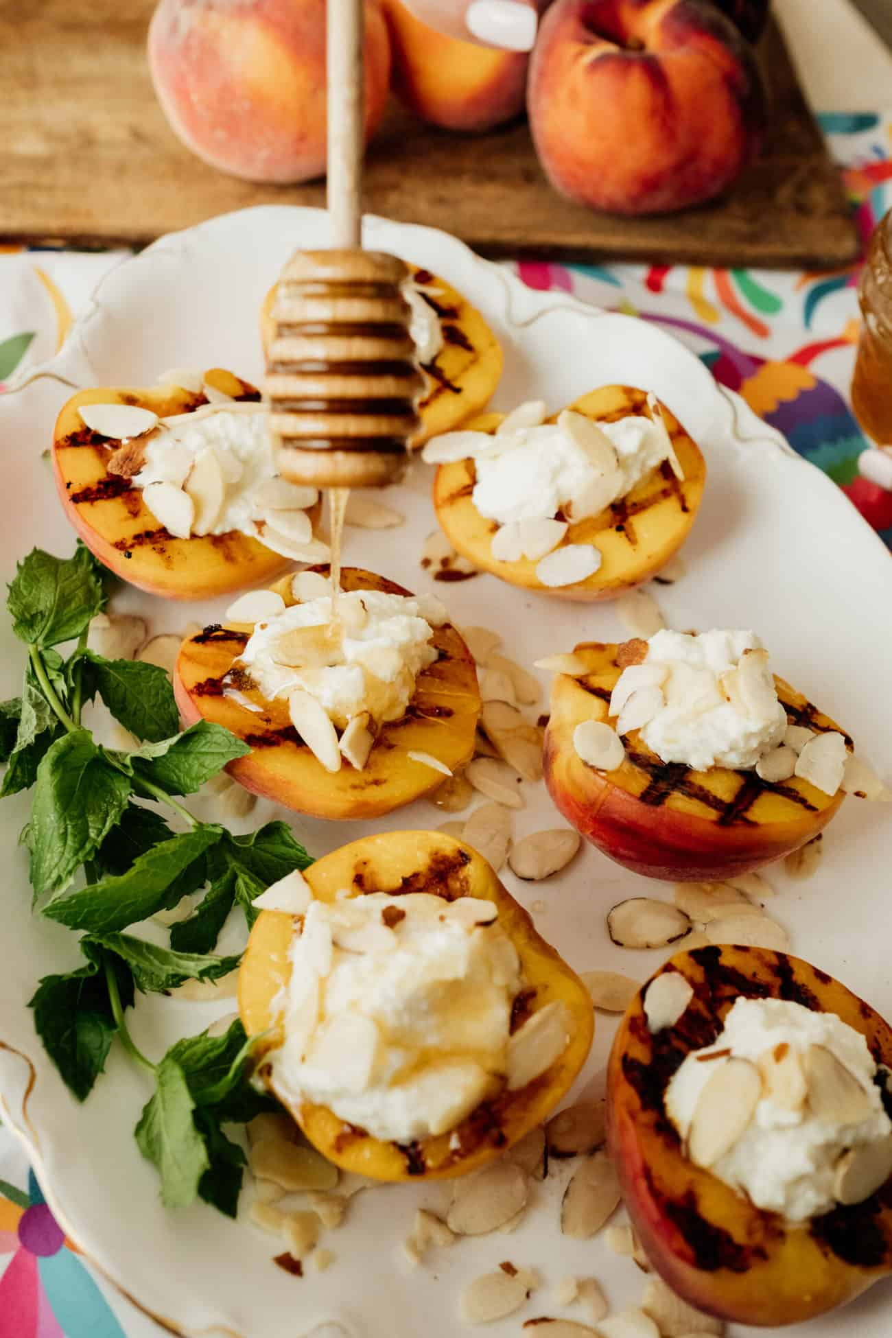 Duraznos al Grill con Requeson (Grilled Peaches with Ricotta Cheese) on a white platter drizzled with honey and sprinkled with sliced almonds