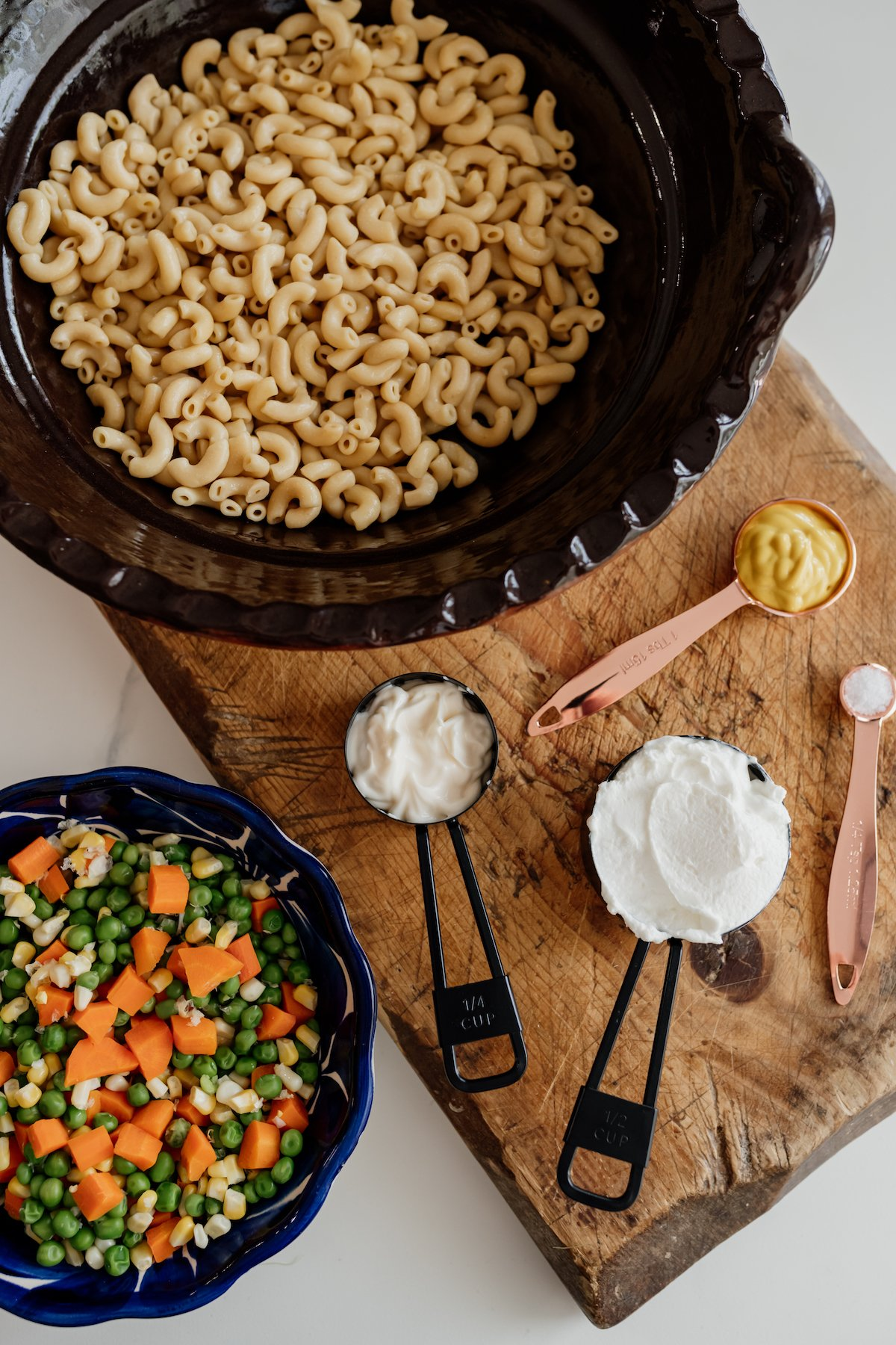cooked macaroni in a brown Mexican bowl, cooked veggies in a blue bowl, and measuring cups and spoons with dressing ingredients on a wooden board