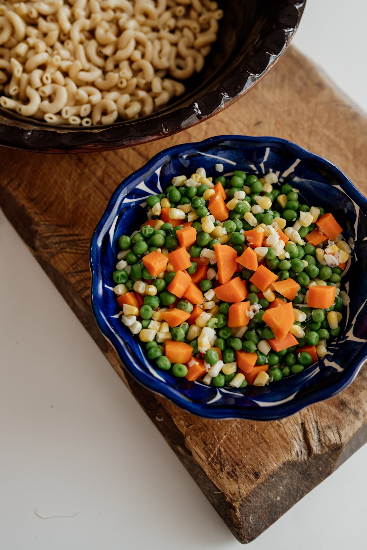 a Mexican blue bowl filled with cooked carrots, peas, and corn and cooked macaroni in a bowl in the background