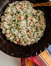 Ensalada de Coditos (Macaroni Salad) in a Mexican brown barro bowl with wooden spoon and striped napkin