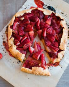 Rhubarb and Strawberry Crostata on a parchment sheet with a slice cut out