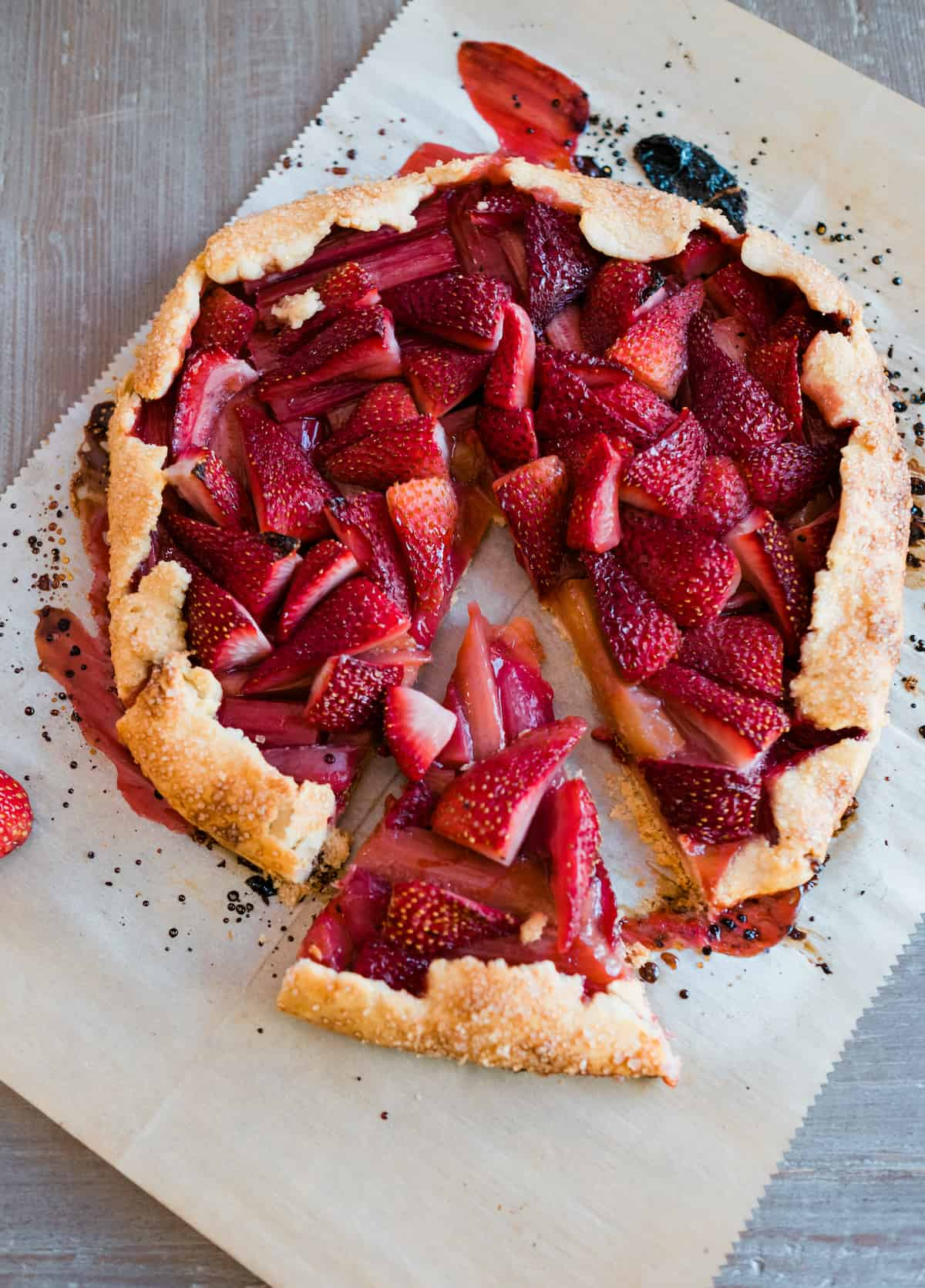 overhead shot of rhubarb strawberry crostata on a piece of parchment with a slice removed
