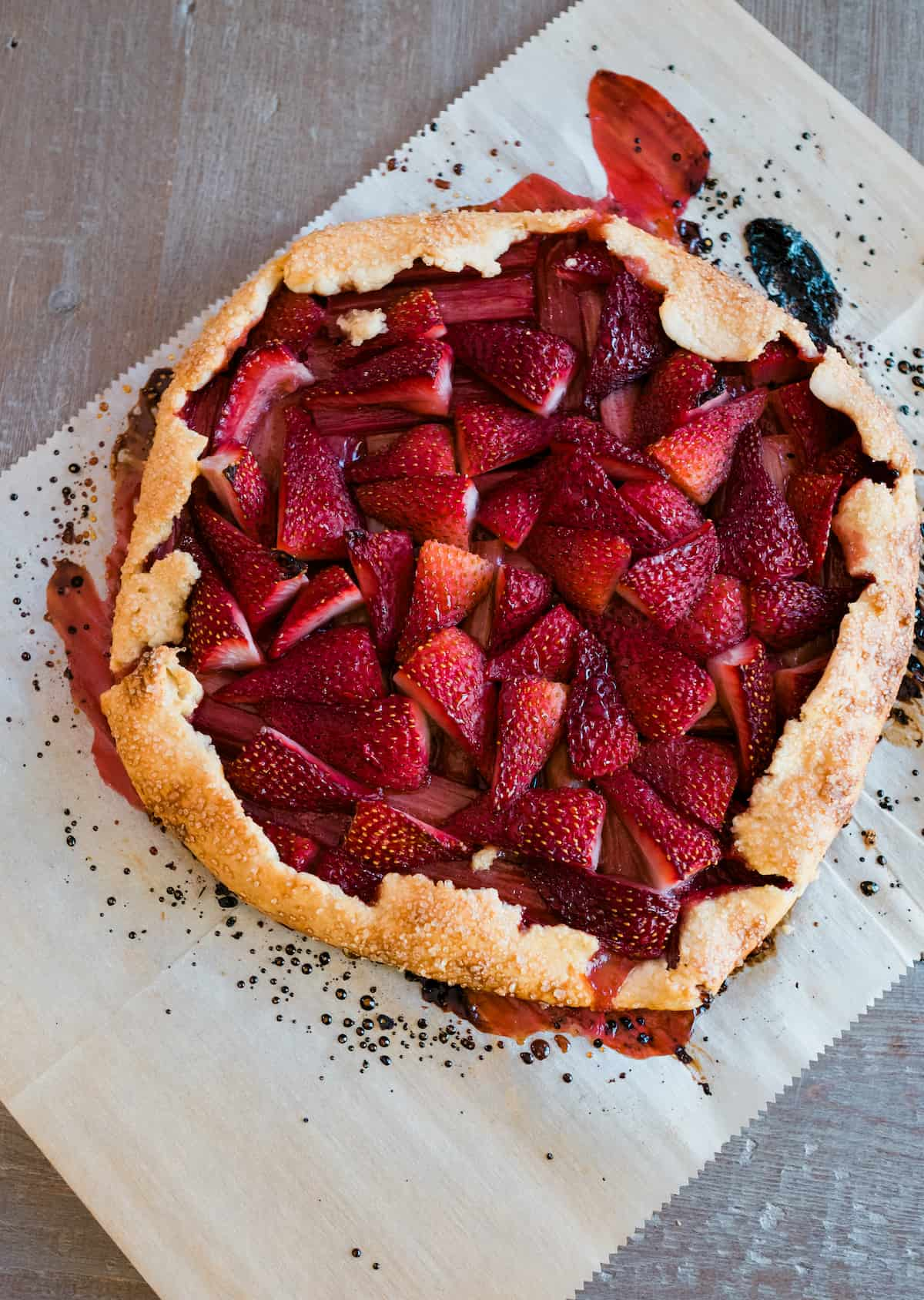 overhead shot of baked strawberry rhubarb crostata on a piece of parchment paper