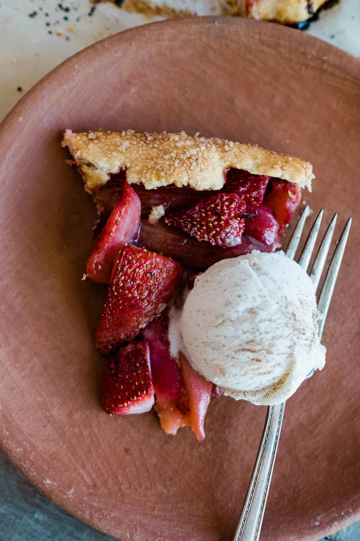 slice of rhubarb strawberry crostata on a terracotta plate with a scoop of vanilla ice cream