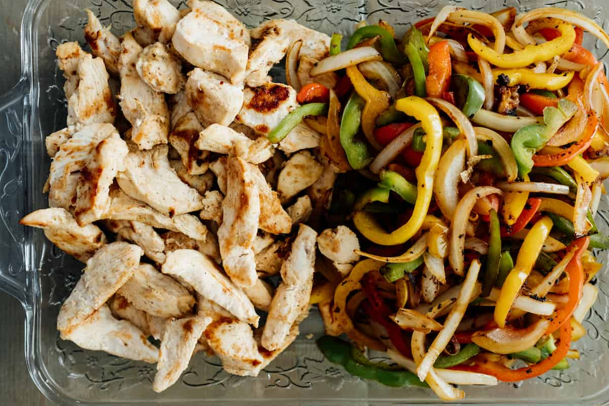 cooked chicken and bell peppers in a dish for fajitas