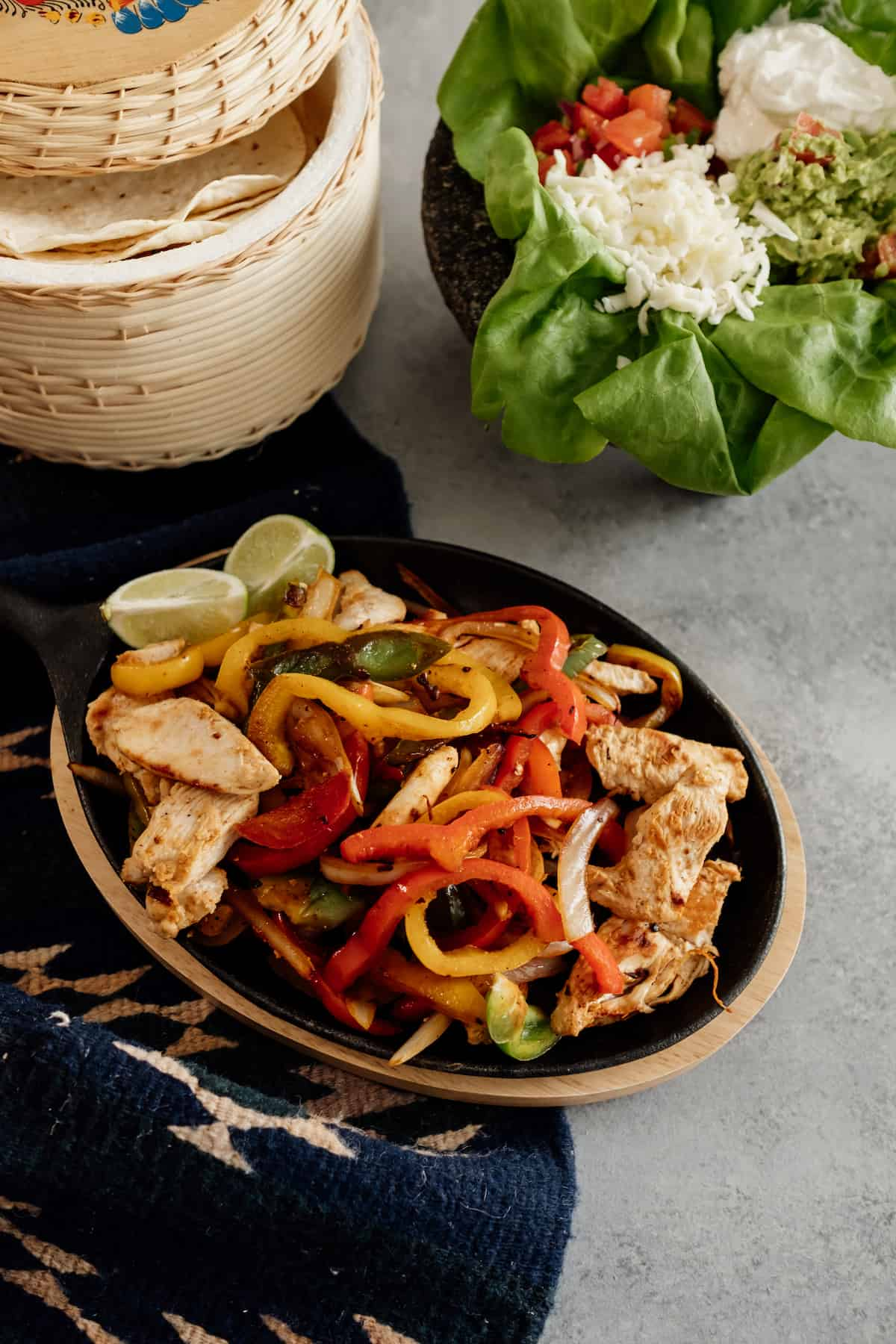 chicken fajitas on a  Cast Iron Fajita Set, Sizzling Skillet, Japanese Steak Plate with flour tortillas in a tortilla warmer and a molcajet filled with toppings