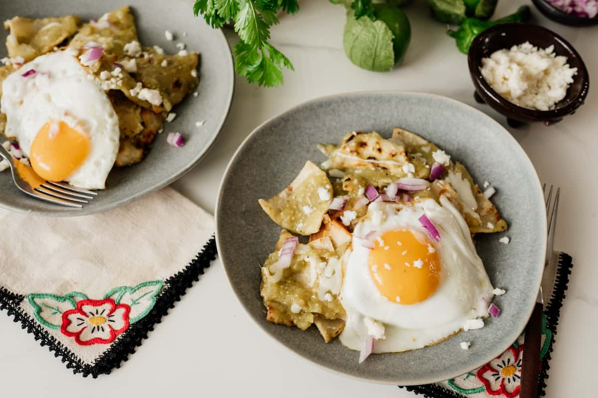 two servings of chilaquiles verdes with fried eggs
