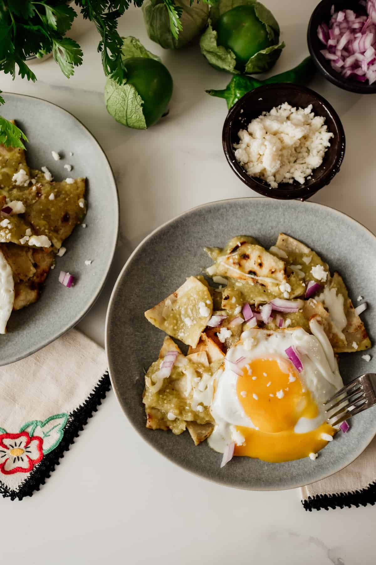 two gray plates with Chilaquiles Verdes and fried eggs with Queso fresco and red onion in the background