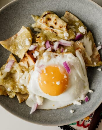 chilaquiles verders on a gray plate with a fried egg on top