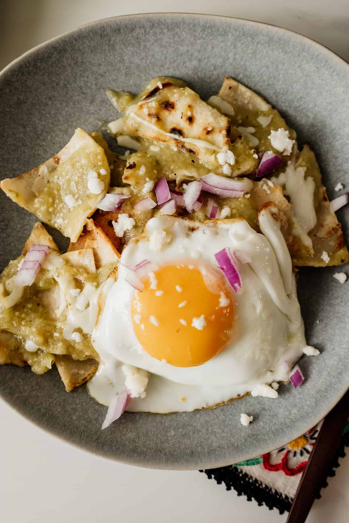 chilaquiles verde on a gray plate topped with a fried egg