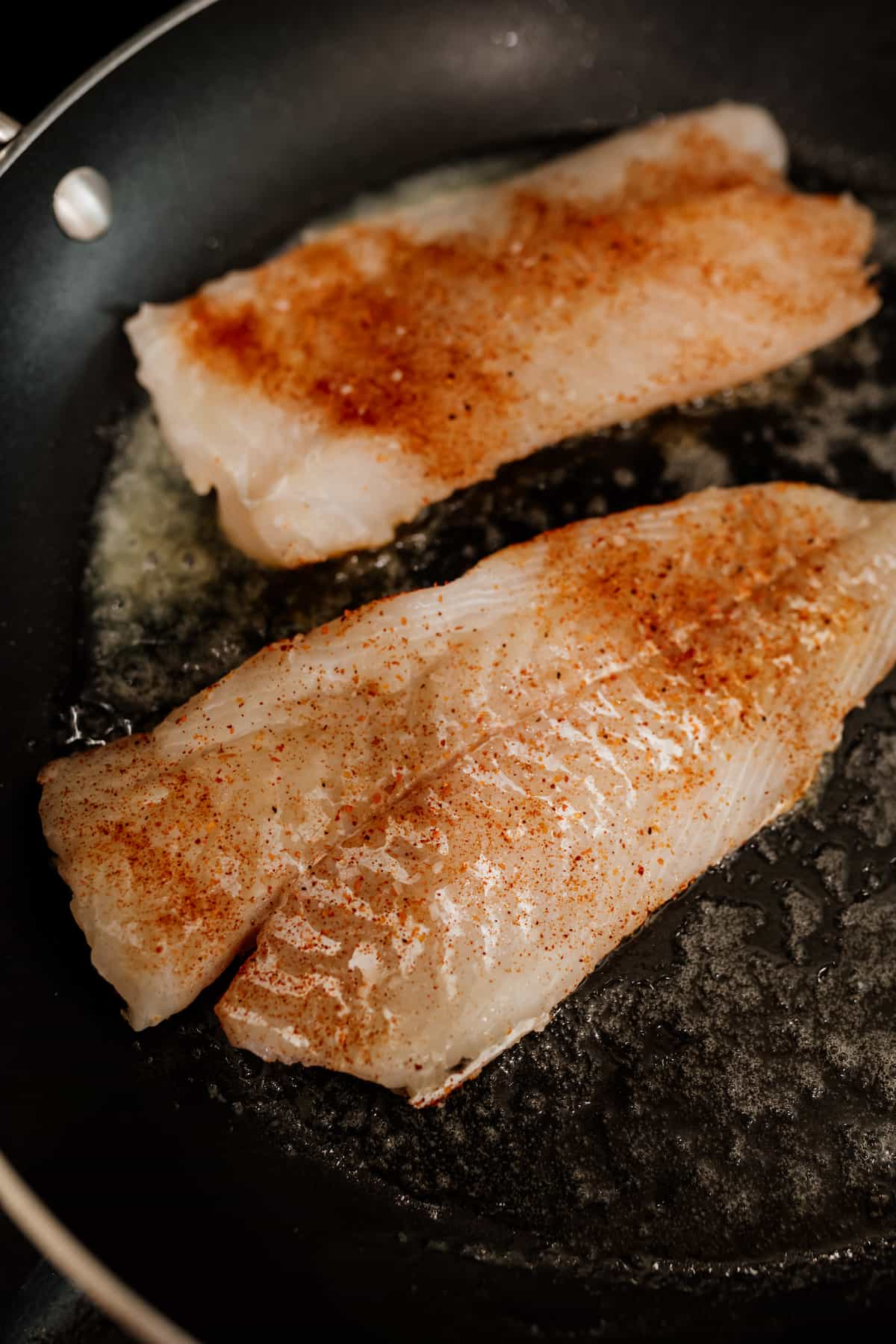 cod fish being cooked on a skillet with butter