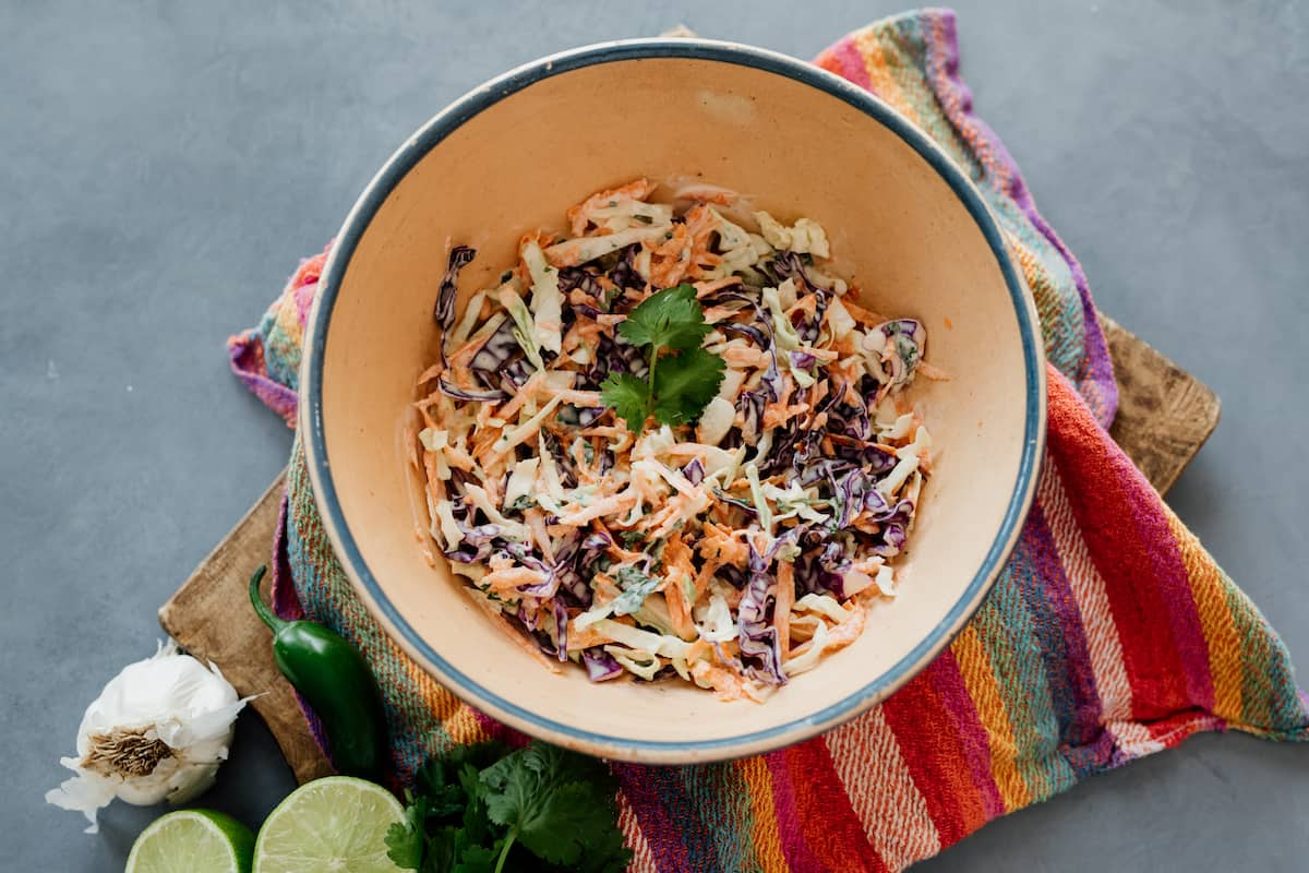 homemade coleslaw in a beige bowl under a colorful striped napkin