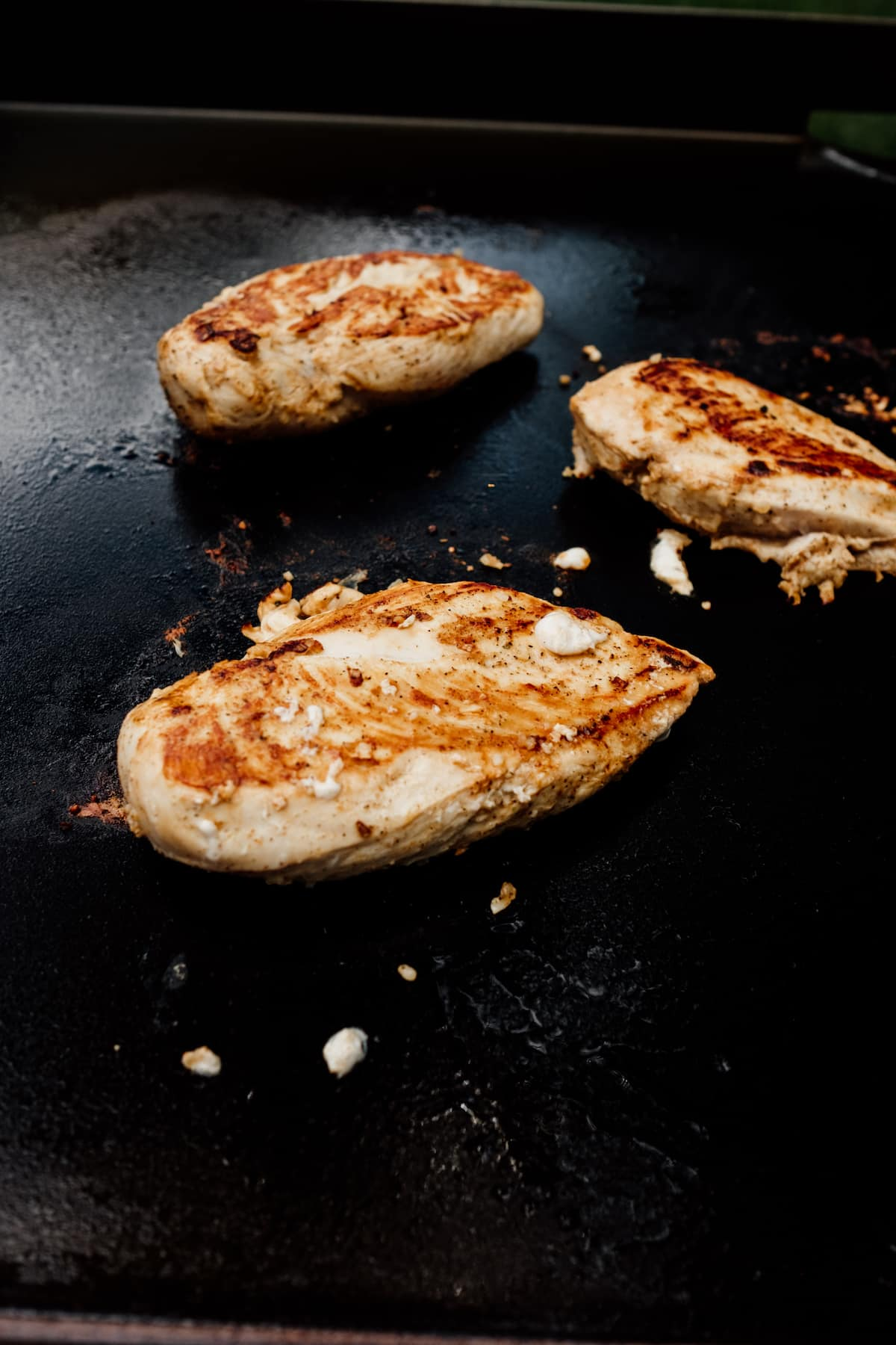Grilled chicken breasts on flat top griddle