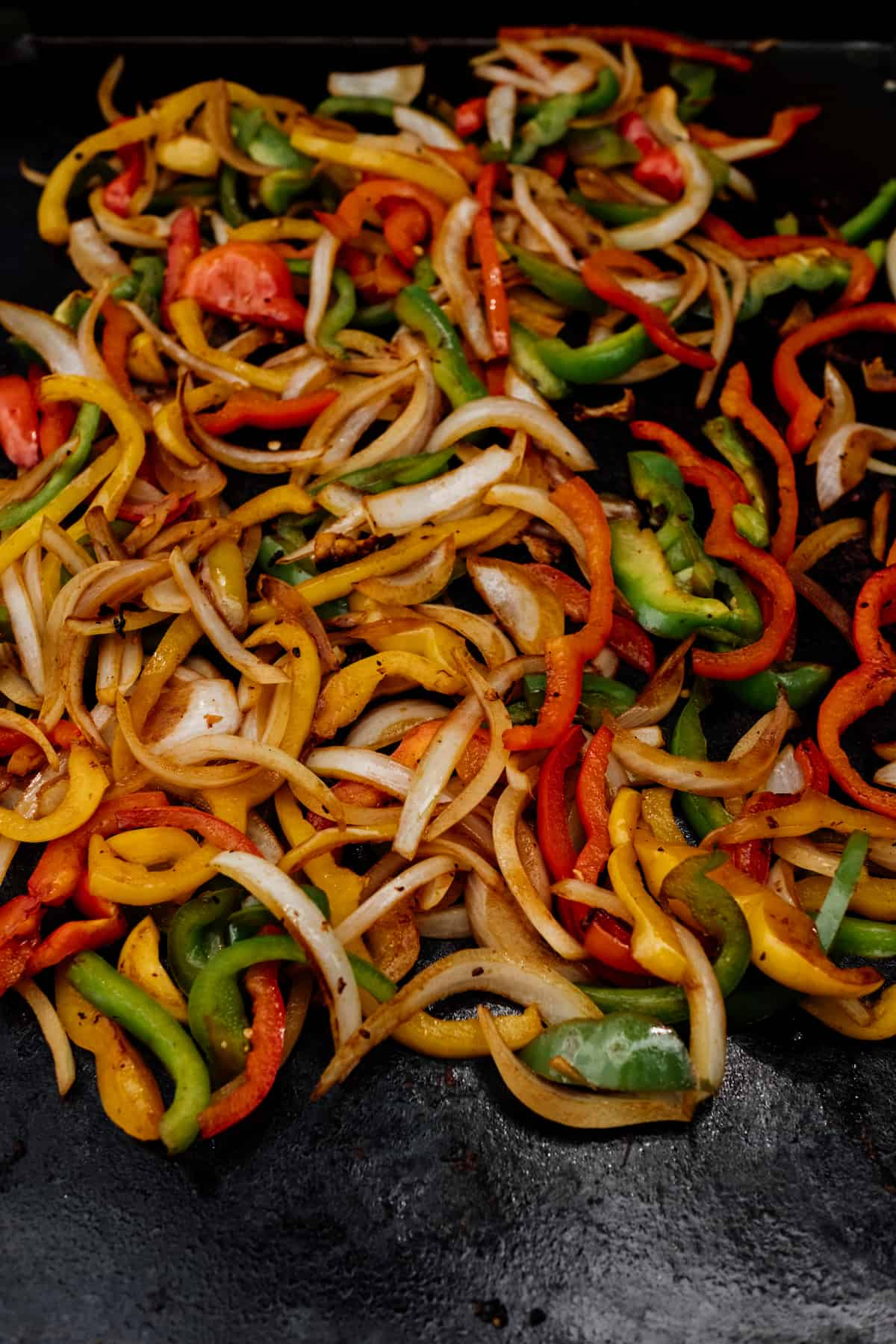 cooked colorful bell peppers and onions on a griddle
