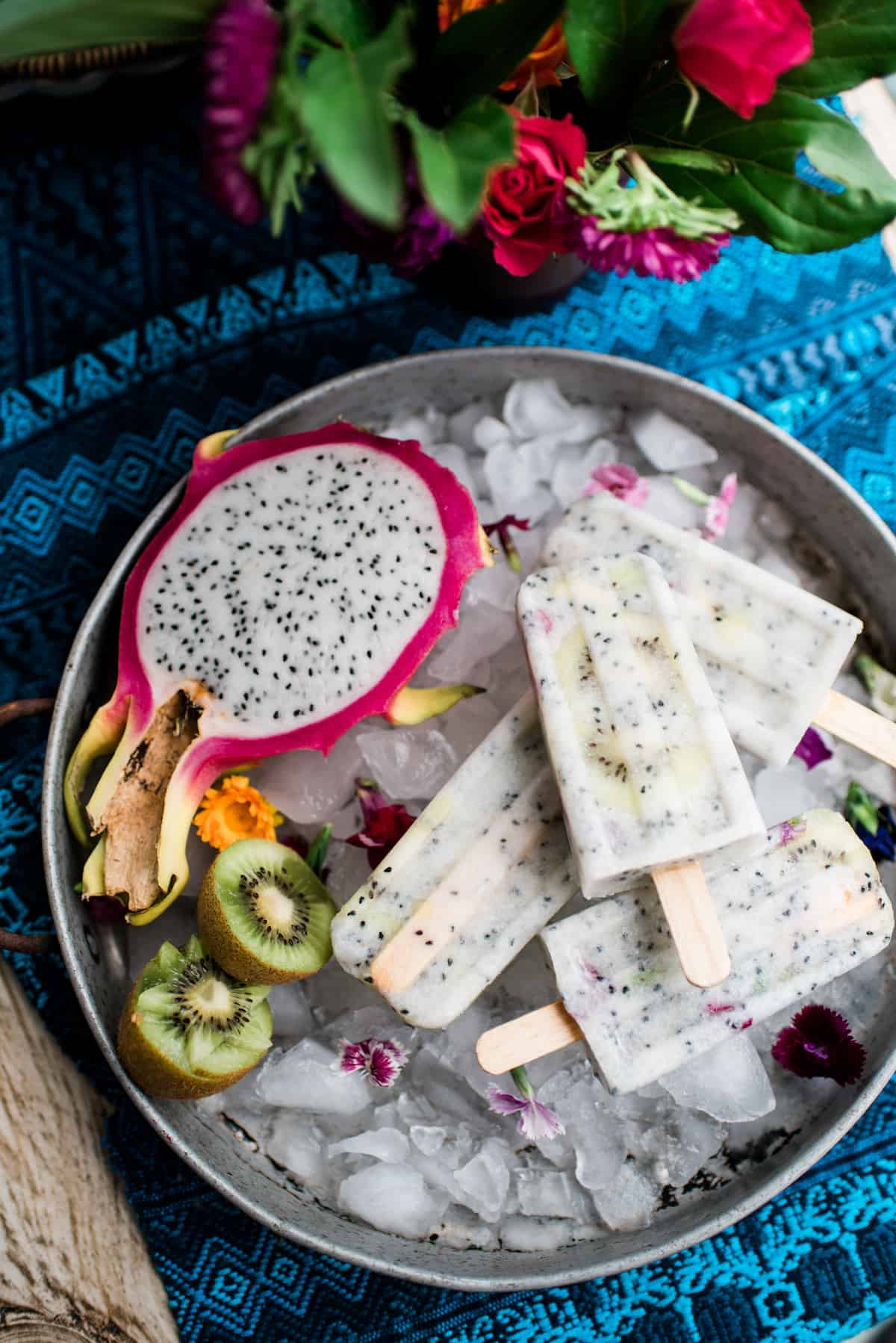 kiwi and dragron fruit paletas on ice in a silver metal tray with a blue runner underneath and flowers in the background