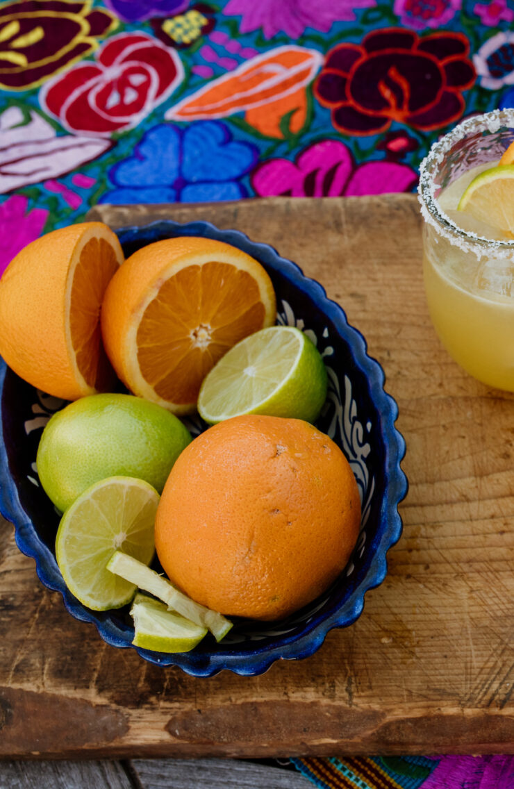 fresh oranges and limes in a bowl on a wooden board and colorful textile and a margarita on the side