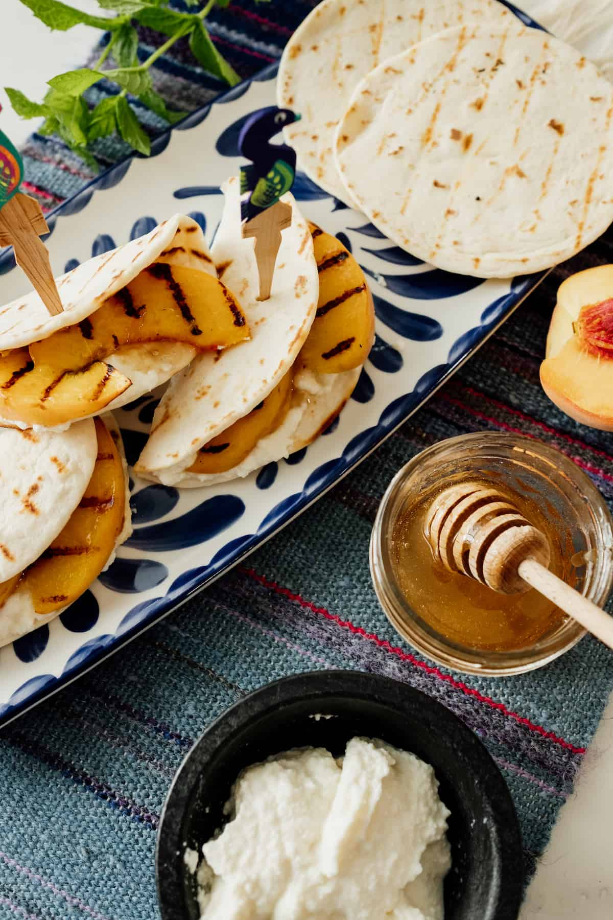Mini Tortillas with Ricotta Cheese and Grilled Peaches on a blue and white Mexican tray and wooden toothpick from Mexico