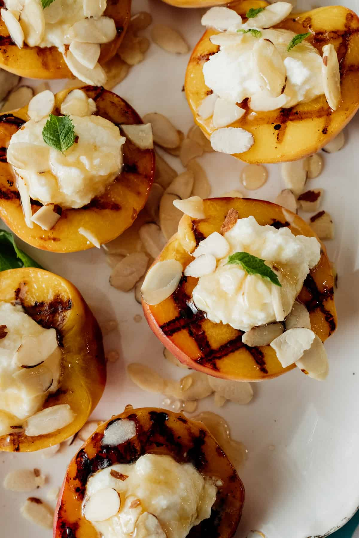 close up of grilled peach halves topped with ricotta cheese, honey, almonds, and mint