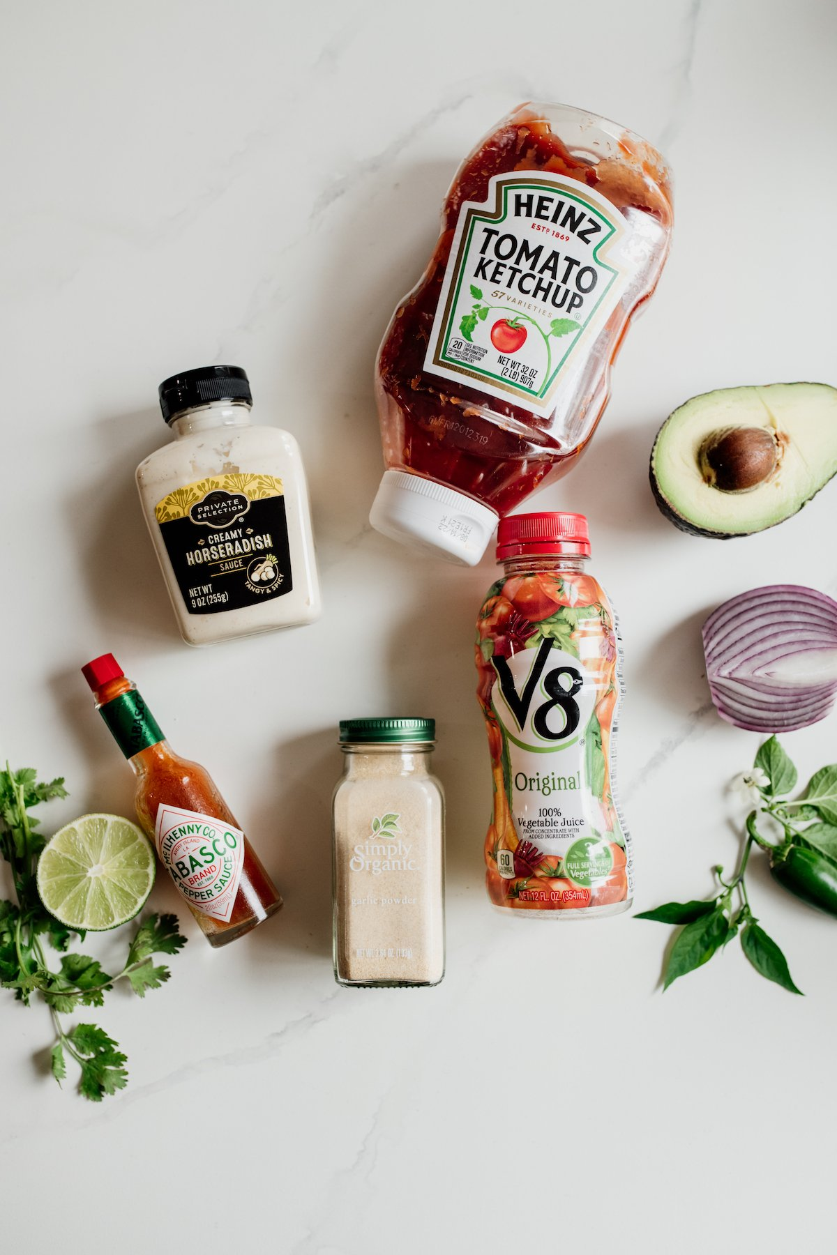 flat lay shot of horseradish, ketchup, v8, and other ingredients for mexican shrimp cocktail