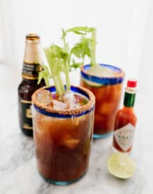 two Michelada beer cocktails with a beer and tabasco on the side