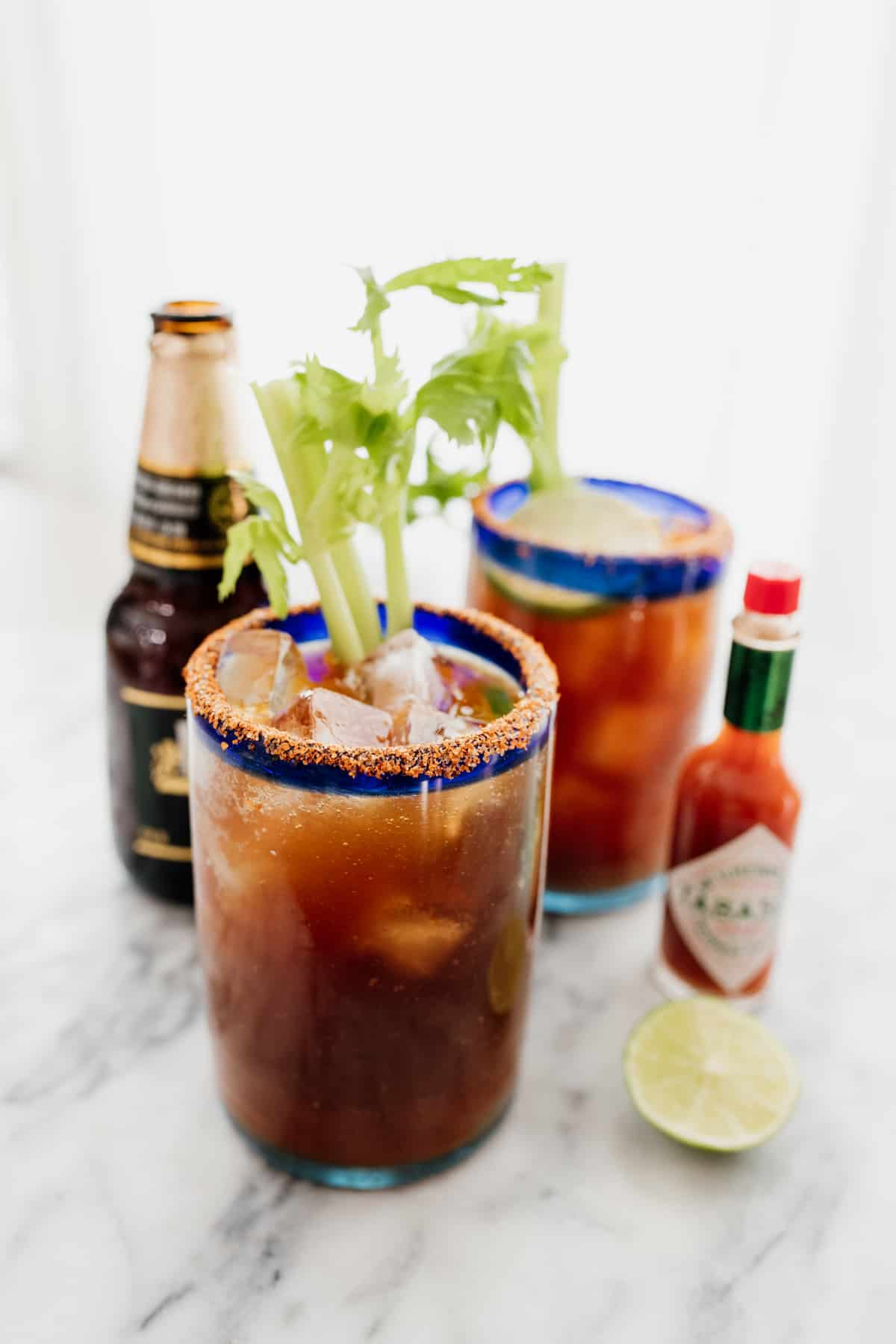 Mexican beer cocktail in two michelada glasses with tabasco and beer on the side