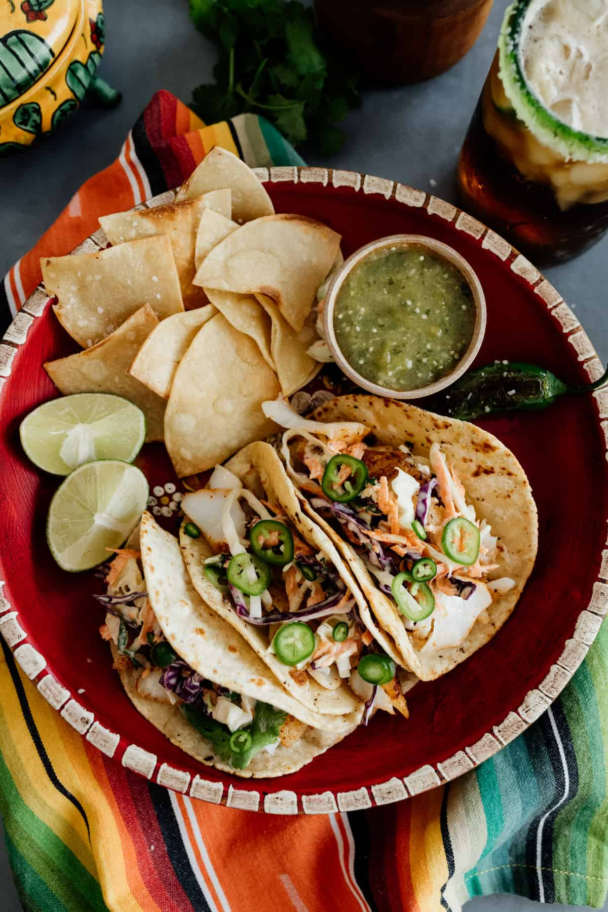 Cod fish tacos with slaw in a red bowl with a side of tortilla chips and salsa verde and a dark beer with a colorful serape napkin