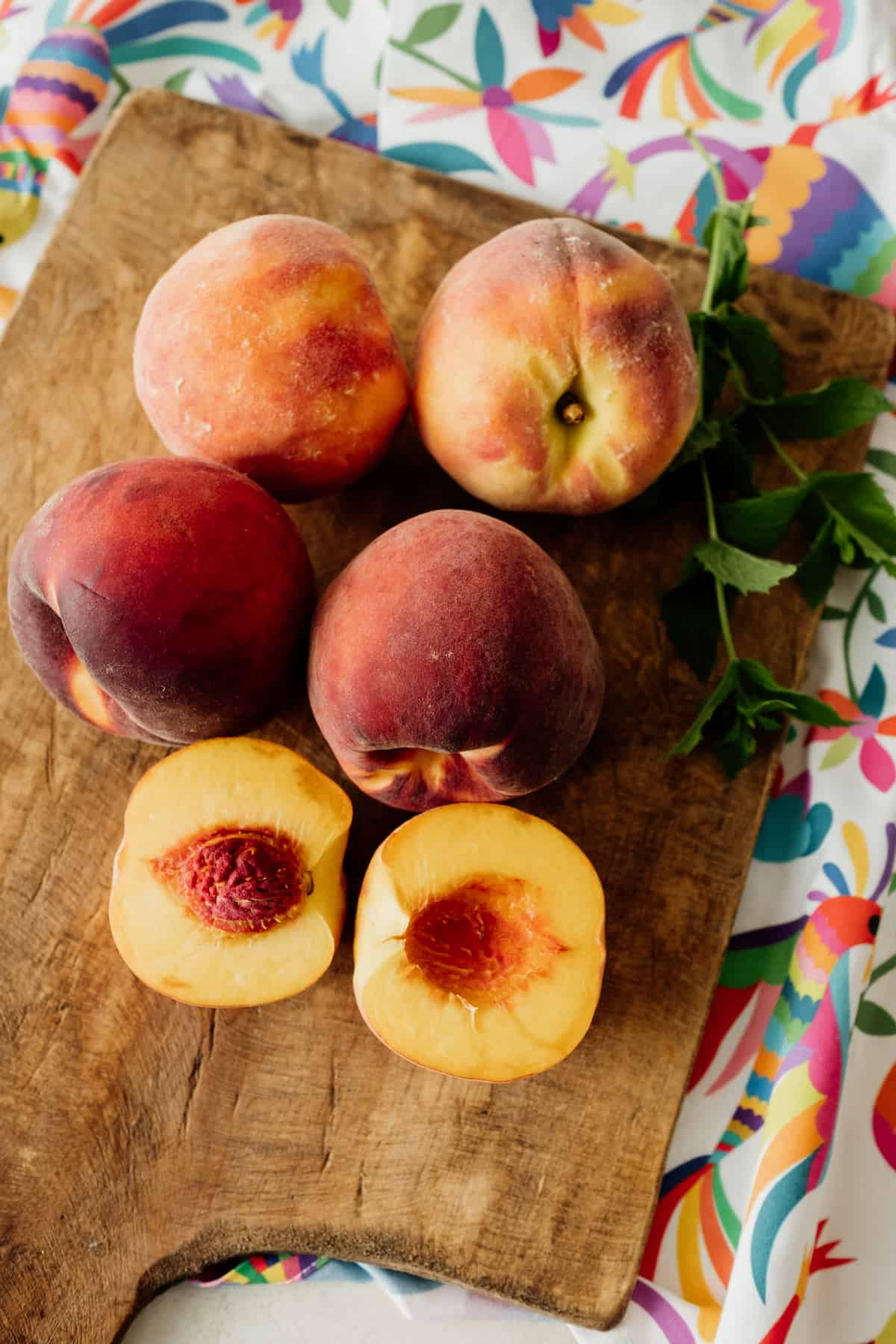 peaches on a wooden board with Otomi fabric below wooden board