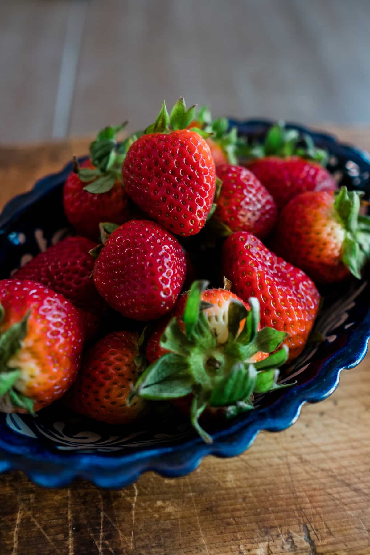 blue fluted bowl filled with fresh strawberries