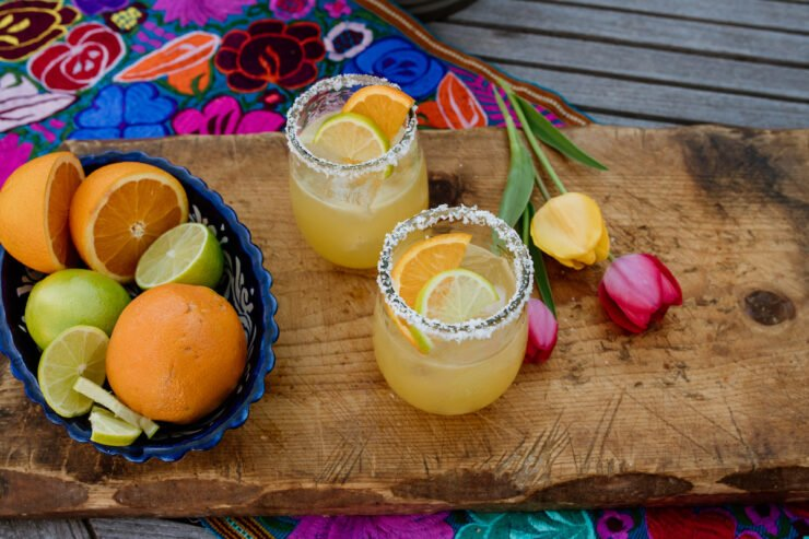 two glasses of margaritas on a wooden board with tulips on the side and a bowl of fresh citrus