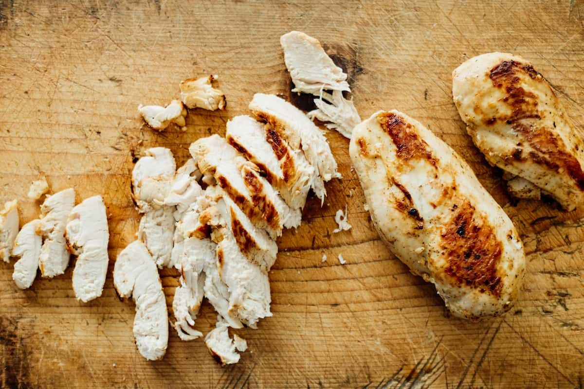 sliced grilled chicken on a wooden board