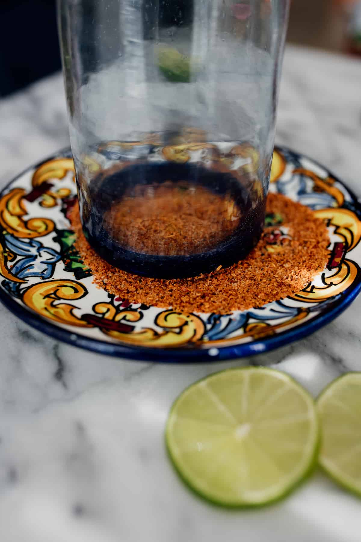 rimming a Mexican hand blown glass with Tajin on a plate for a beer cocktail